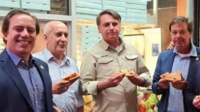 Impedido de entrar em restaurante, Bolsonaro come Pizza na rua